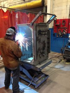 Metal Working Group Welding a Custom Rack for Fixtures